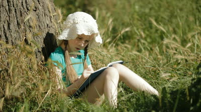 stock-footage-child-reading-a-book-in-nature-against-a-tree-then-looks-up-and-smiles-to-camera